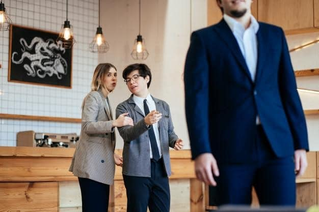 A photo of two employees gossiping behind another employee's back, illustrating the concept of workplace harassment.