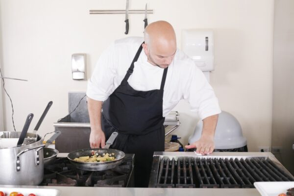 A professional chef cleaning the kitchen.